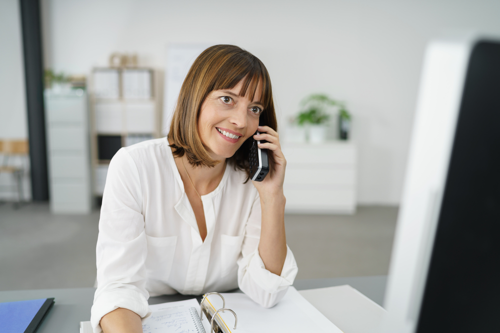Happy Businesswoman at her Table, Talking to Someone Using her Mobile Phone
