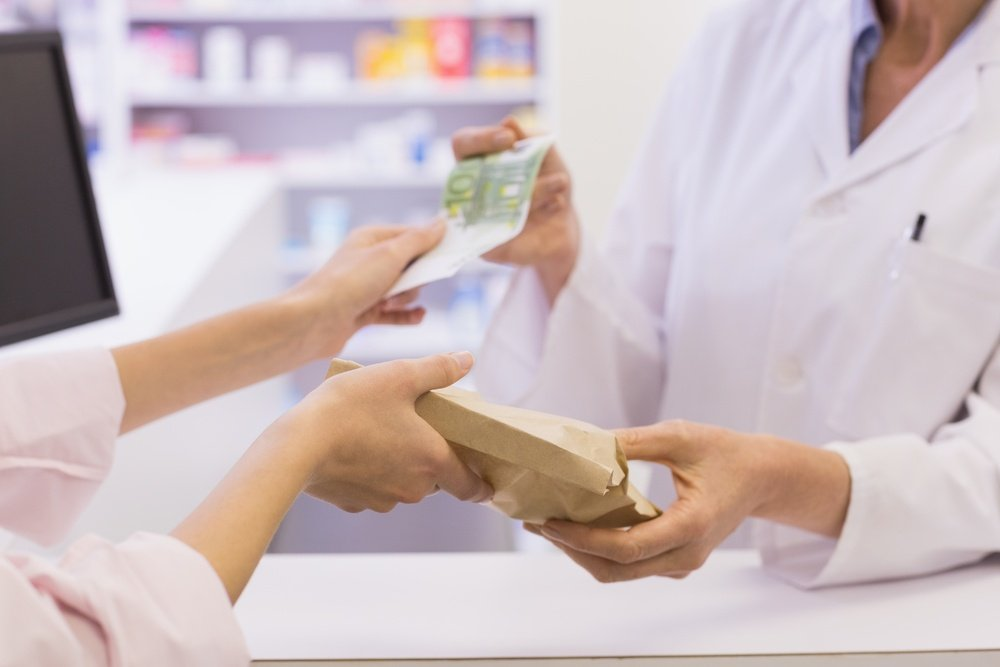 Pharmacist giving medicine to costumer at pharmacy