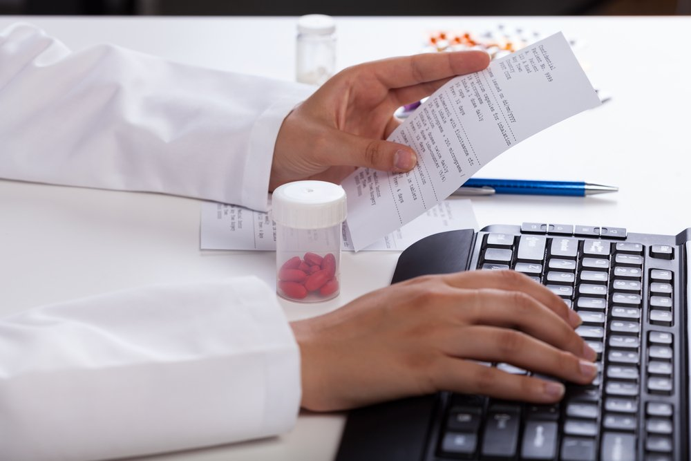 Pharmacist's hands checking information about medicines