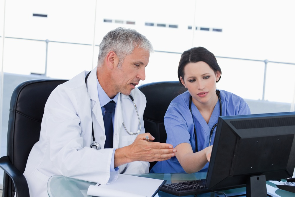 Professional medical team working with a computer in an office