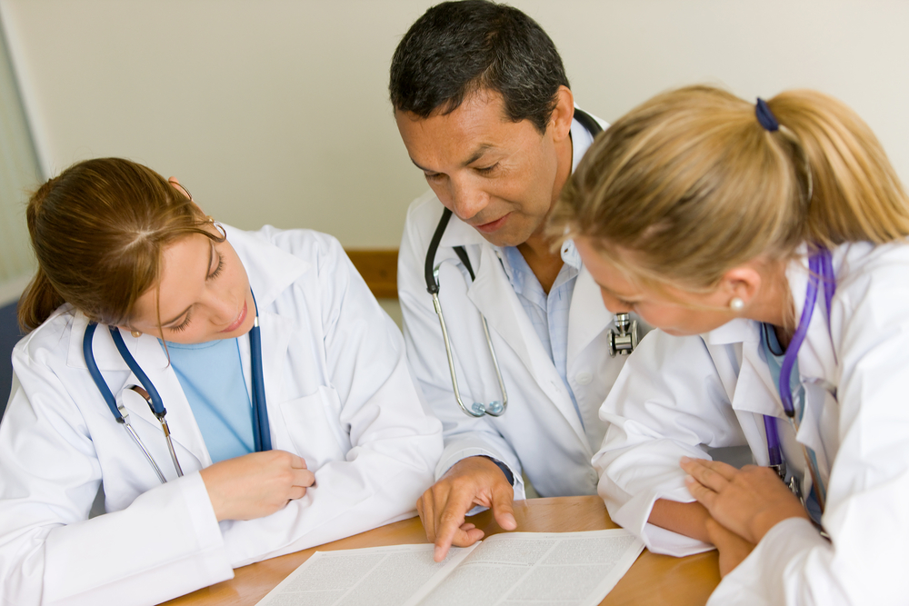 small group of doctors in a meeting discusing a medical history