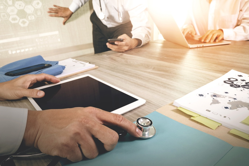 Medicine doctor hand working with modern computer and digital pro tablet with blank screen with his team on wooden desk as medical concept